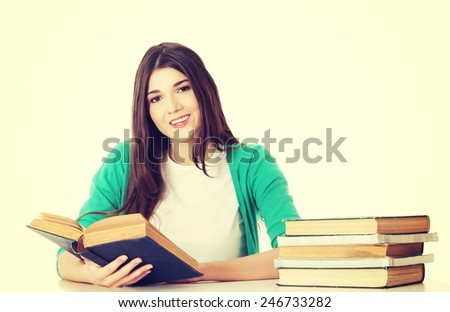 Young beautiful student sitting and reading a book.