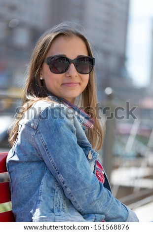 Young beautiful stylish girl in sunglasses on a sunny day on the streets