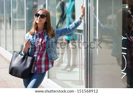Young beautiful stylish girl in sunglasses on a sunny day on the streets - stock photo
