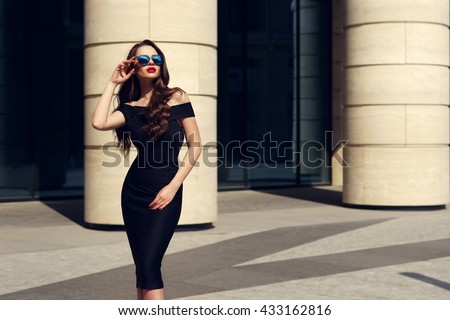 Young beautiful stylish girl posing at summer city streets on a sunny day. Stunning woman wearing black dress and sunglasses. Pretty model with long curly hair and red lips - stock photo