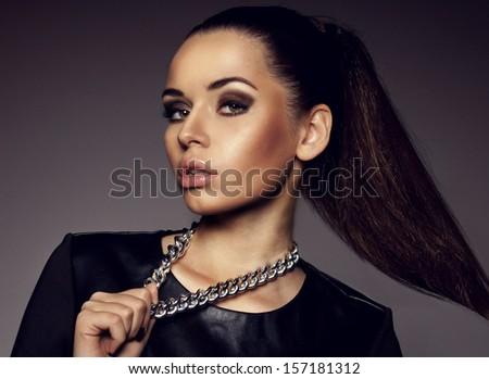 Young beautiful stylish girl wearing black leather dress and metal chain. Rock style studio beauty portrait of pretty fashion model - stock photo