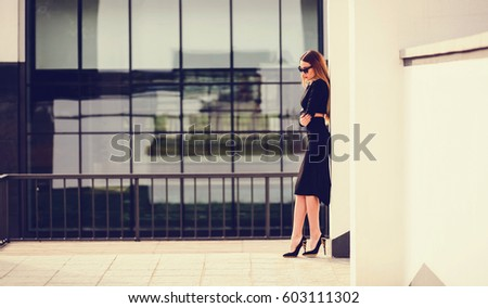 Young beautiful stylish woman posing in black dress in city. Copy space