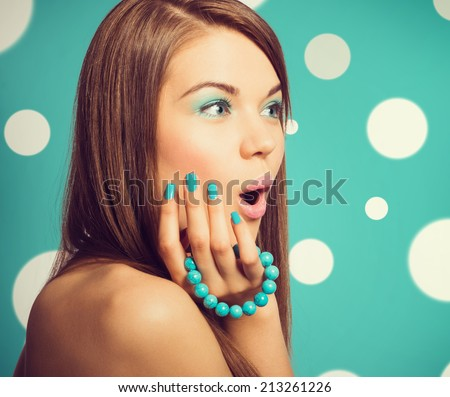 Young beautiful surprised woman holding a turquoise bracelet with bright color manicure and makeup. Vintage styled colors.