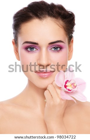 Young beautiful tanned woman with fresh make-up and gorgeous pink orchid, over white background - stock photo