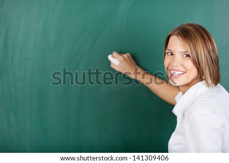 Young beautiful teacher holding a chalk and writing on the blackboard - stock photo