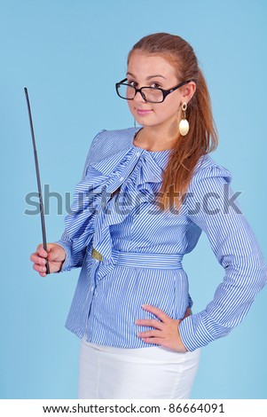 Young beautiful teacher in blue blouse wearing glasses standing and holding pointer - stock photo