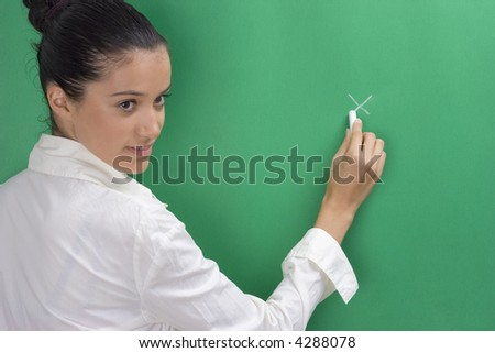 young beautiful teacher in white on green background - stock photo