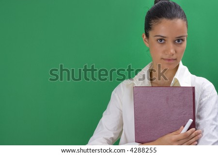 young beautiful teacher on green background - stock photo