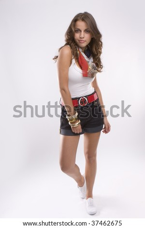 Young beautiful teen girl isolated on white walking wearing red belt and shorts