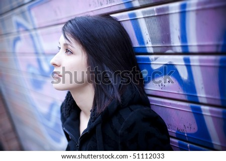 Young beautiful teen in pensive gesture in street background. - stock photo