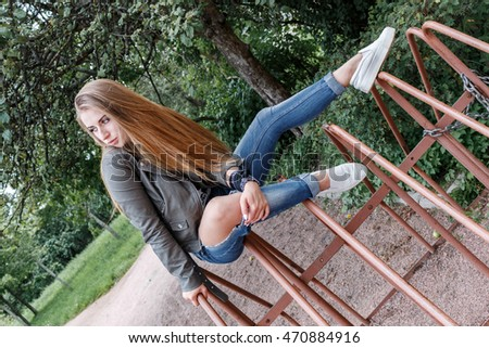 young beautiful teenager girl is sitting on metal rods, bicycle parking, rock 'n' roll. rock style