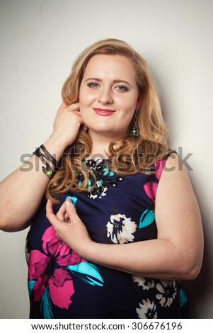 Young beautiful thick blonde woman in a motley vintage dress - stock photo