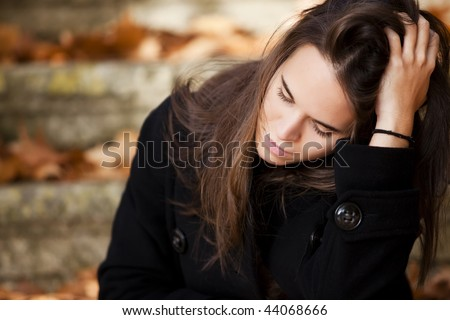 Young beautiful thoughtful girl in autumn background - stock photo