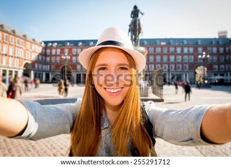 young beautiful tourist woman visiting Europe in holidays exchange students and taking selfie picture  in town smiling happy on sunny day in travel and vacation concept - stock photo