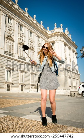 young beautiful tourist woman visiting Europe on holidays exchange students and taking selfie picture  in town happy on sunny day in travel and vacation concept - stock photo