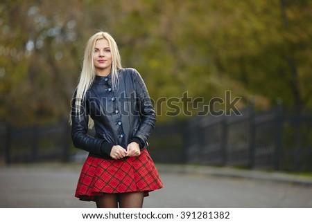Young beautiful trendy dressed blonde woman posing outdoors against blurry foliage background looking into camera - stock photo