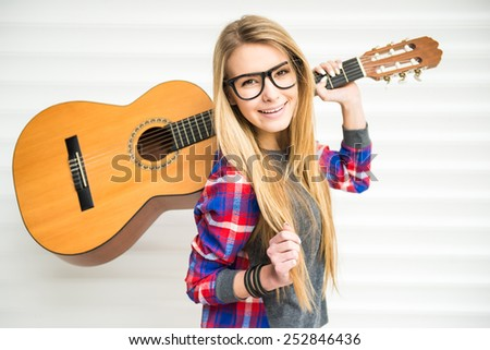 Young beautiful, trendy girl with acoustic guitar is looking at the camera and smiling. - stock photo