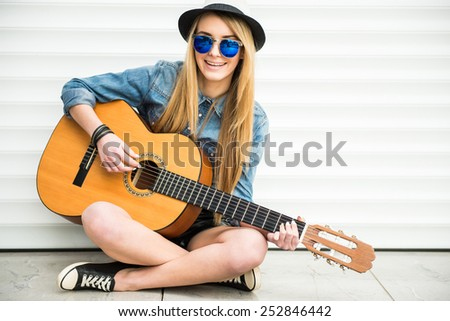 Young beautiful, trendy girl with acoustic guitar is playing sitting on the floor. - stock photo