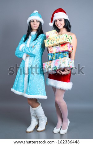 Young beautiful twin santa girl holding christmas presents in santa hats with black hair and makeup in studio