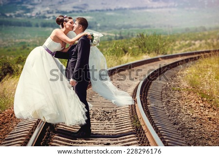 Young beautiful wedding couple on railway - stock photo