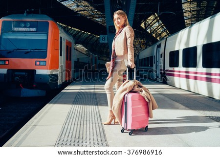 young beautiful well-dressed businesswoman with a pink suitcase waiting for the train at the railway station