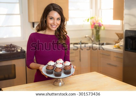 Young beautiful wife woman cook chef baker with fresh batch of cupcakes portrait home sweet homemade - stock photo