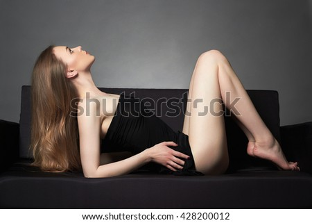 young beautiful woman alone on sofa.Sexy beauty Blond girl - stock photo