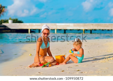young beautiful woman and her daughter playing at sandy beach