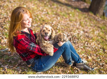 Young beautiful woman and her dog (American Cocker Spaniel) posing outside at fall time