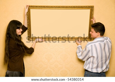 young beautiful woman and smiling man hang up on wall picture in frame, looking at picture