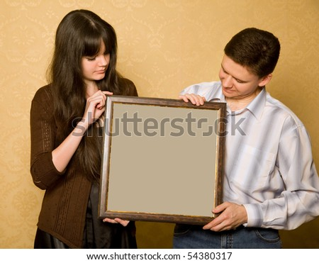 young beautiful woman and smiling man with picture in frame in hands, looking at picture - stock photo