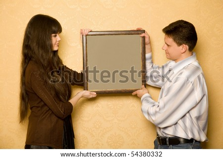 young beautiful woman and smiling man with picture in frame in hands, looking at picture with side - stock photo