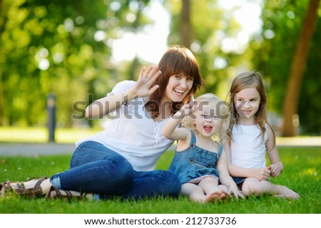 Young beautiful woman and two little kids hugging in summer park on warm and sunny day