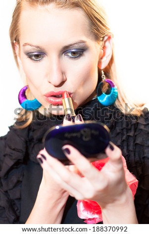 Young beautiful woman applying fashionable colorful party make-up. - stock photo