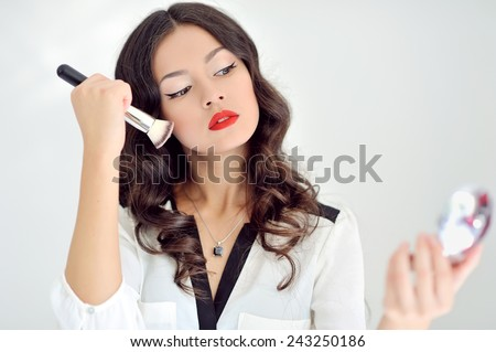 Young beautiful woman applying make-up - stock photo