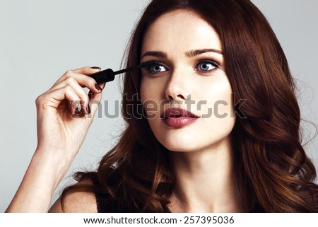 Young beautiful woman applying mascara makeup on eyes by brush - stock photo