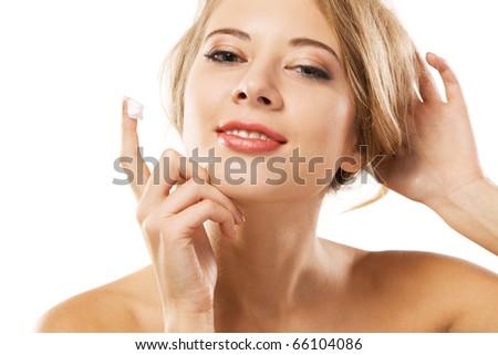 Young beautiful woman applying skin cream, white background - stock photo
