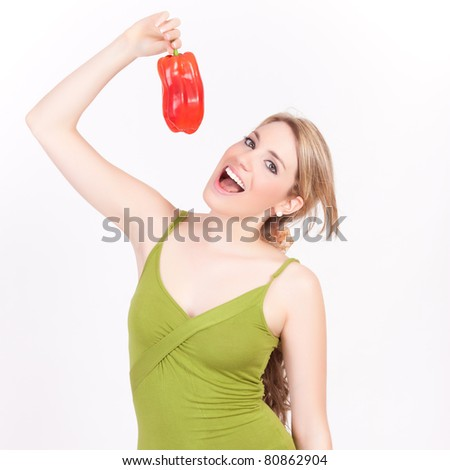 young beautiful woman bites a pepper over her head isolated on white background - stock photo