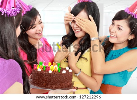young beautiful woman blindfold during surprise birthday party - stock photo