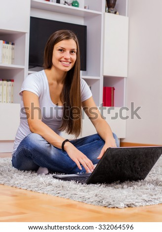 Young beautiful woman, browsing internet, using laptop computer,in casual wear, on floor at home.