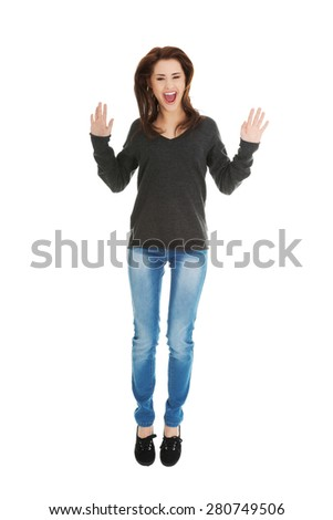 Young beautiful woman cheering and jumping - stock photo