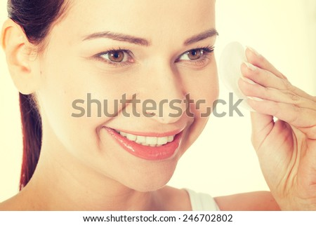 Young beautiful woman cleaning face with cotton pads.
