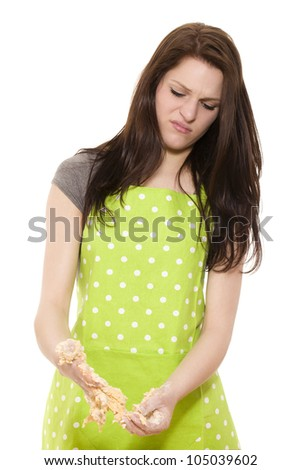 young beautiful woman cleaning her hands from dough on white background - stock photo