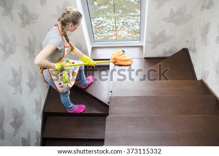 young beautiful woman cleaning wooden stairs by mop - stock photo
