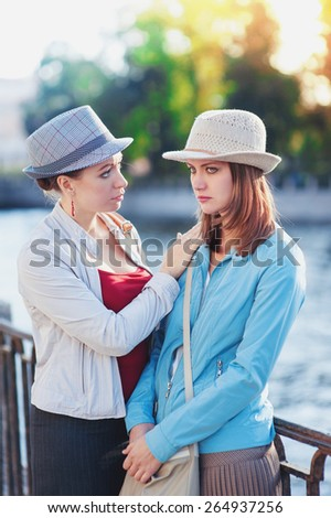 Young beautiful woman comforting her friend in the city outdoor - stock photo