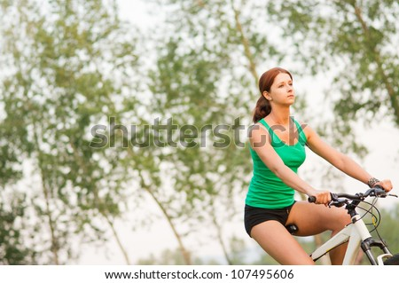 Young beautiful woman cycling in the park - stock photo