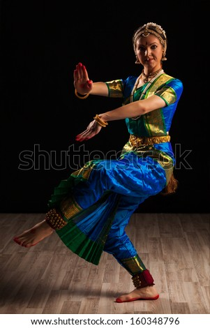 Young beautiful woman dancer exponent of Indian classical dance Bharatanatyam in Shiva pose - stock photo