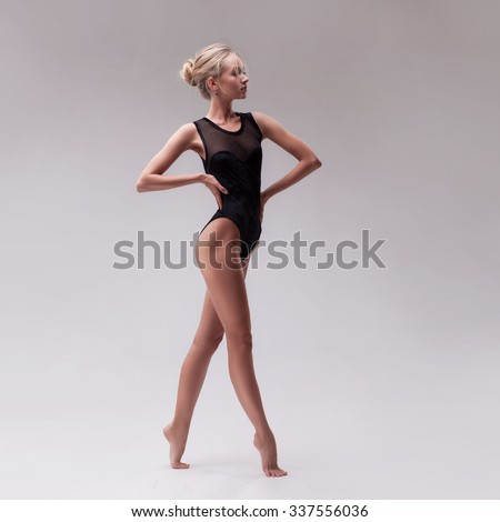 young beautiful woman dancer in black swimsuit posing on a light grey studio background - stock photo