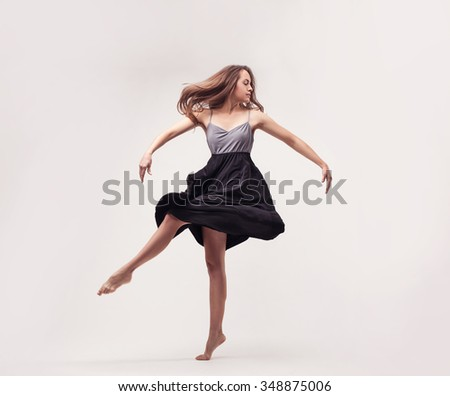 young beautiful woman dancer jumping on a gray studio background