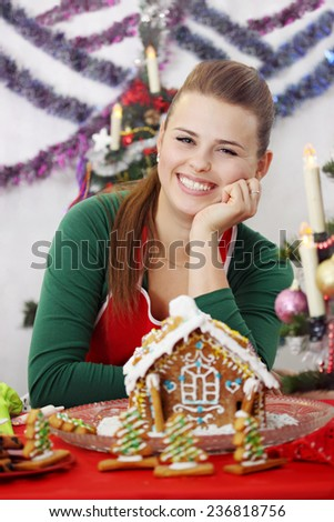 Young beautiful woman decorated gingerbread house - stock photo